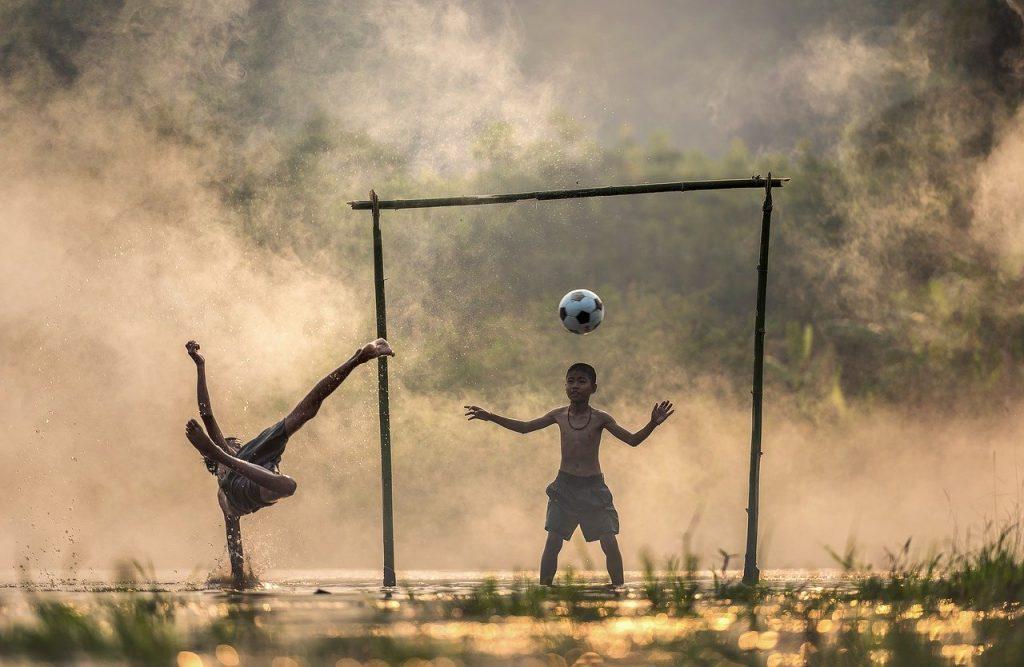 Enfants jouant au foot en extérieur en Asie