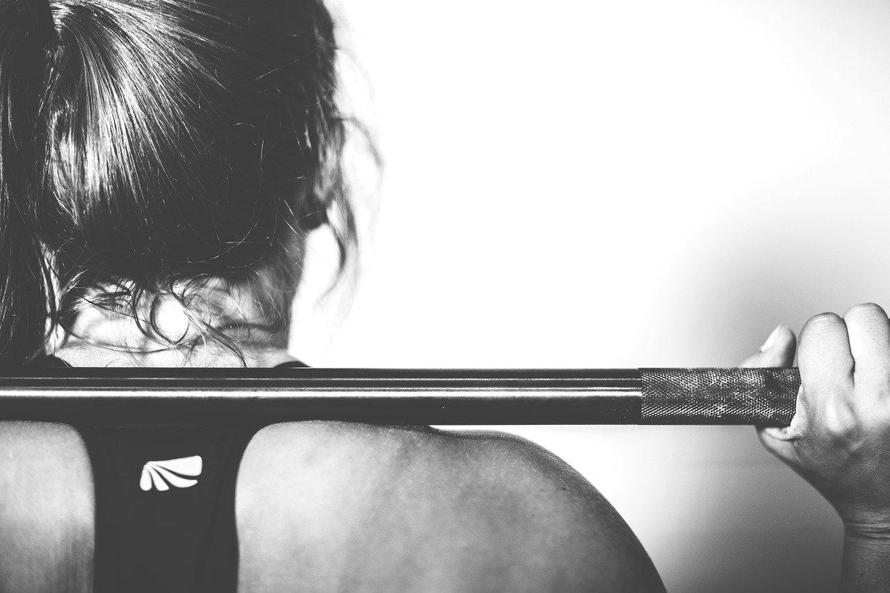 femme faisant du crossfit avec barre de musculation