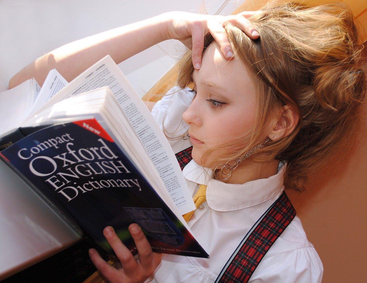 Jeune fille blonde lisant livre d'anglais