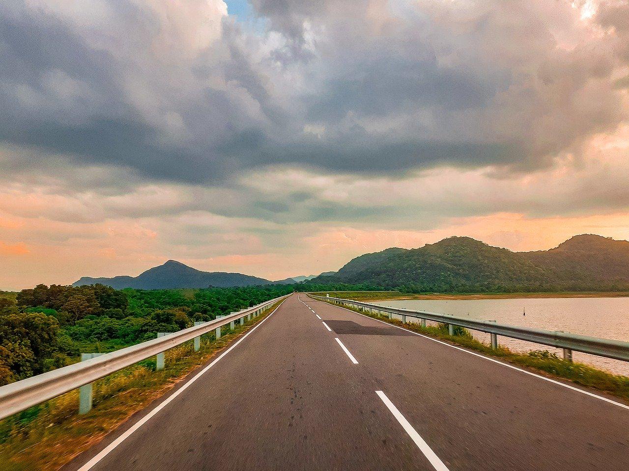 Longue route en fin de journée, près de l'eau