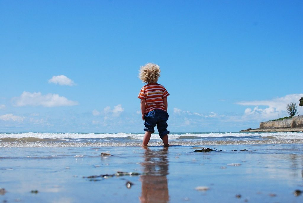 petit garçon blond les pieds dans la mer