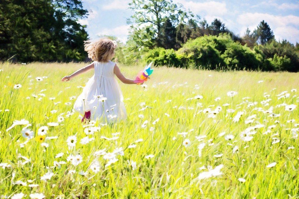 petite fille en robe blanche courant dans un champs