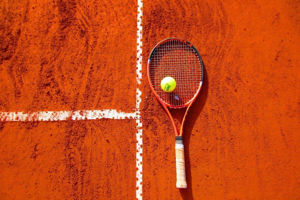raquette et balle de tennis sur un terrain en terre battu