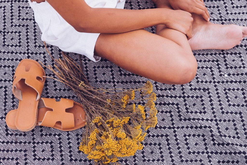 Femme assise sur une couverture à côté de sandale et fleures