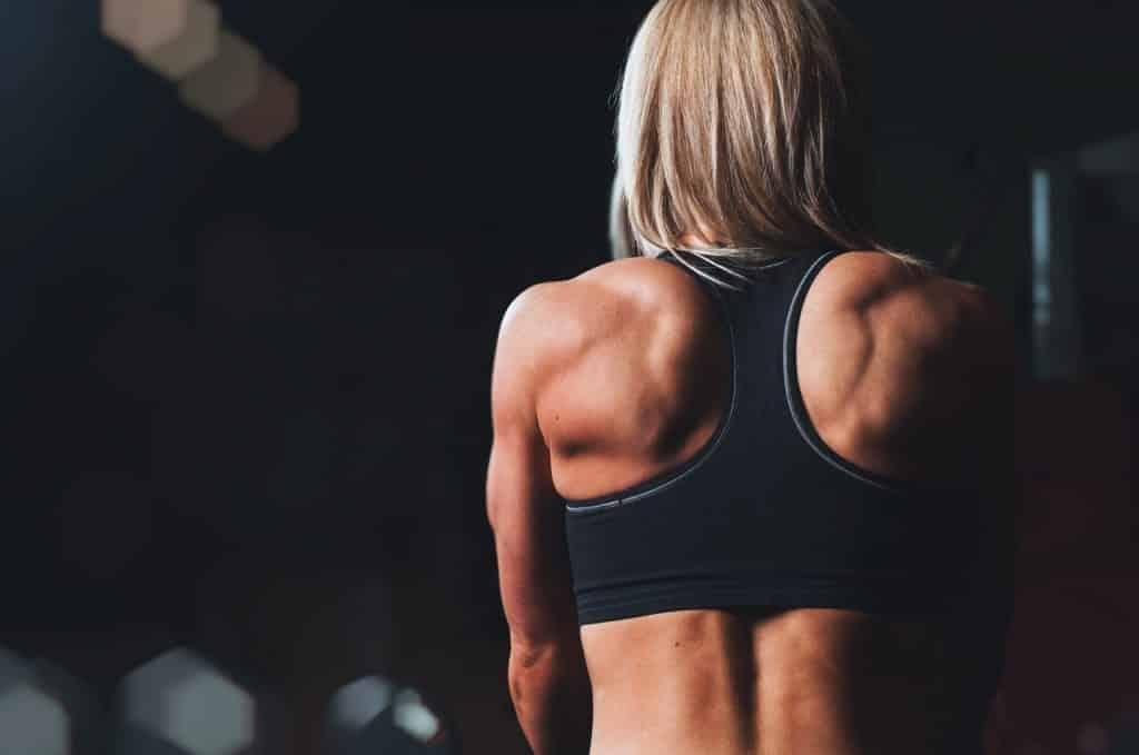 Femme blonde de dos musclée avec brassière