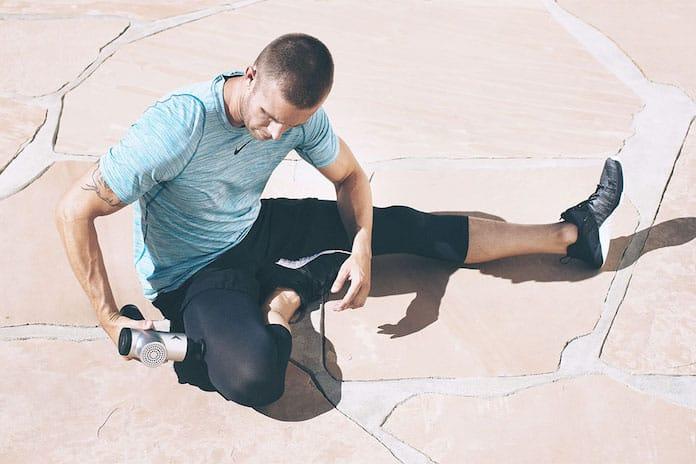 Homme utilisant un pistolet de massage sur ses cuisses en extérieur