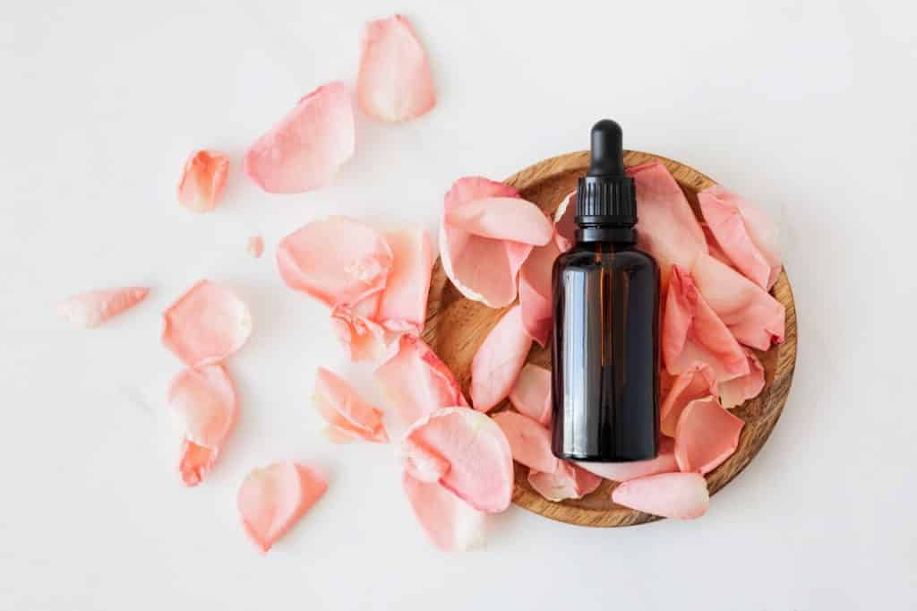 Flacon d'huile sur pétales de rose