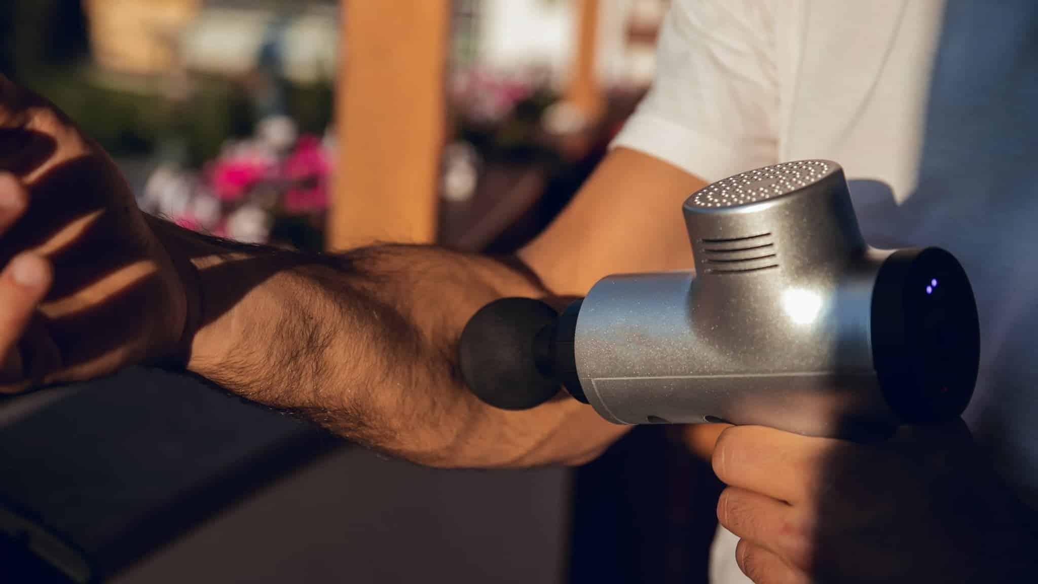 Pistolet de massage utilisé par un homme sur l'avant bras