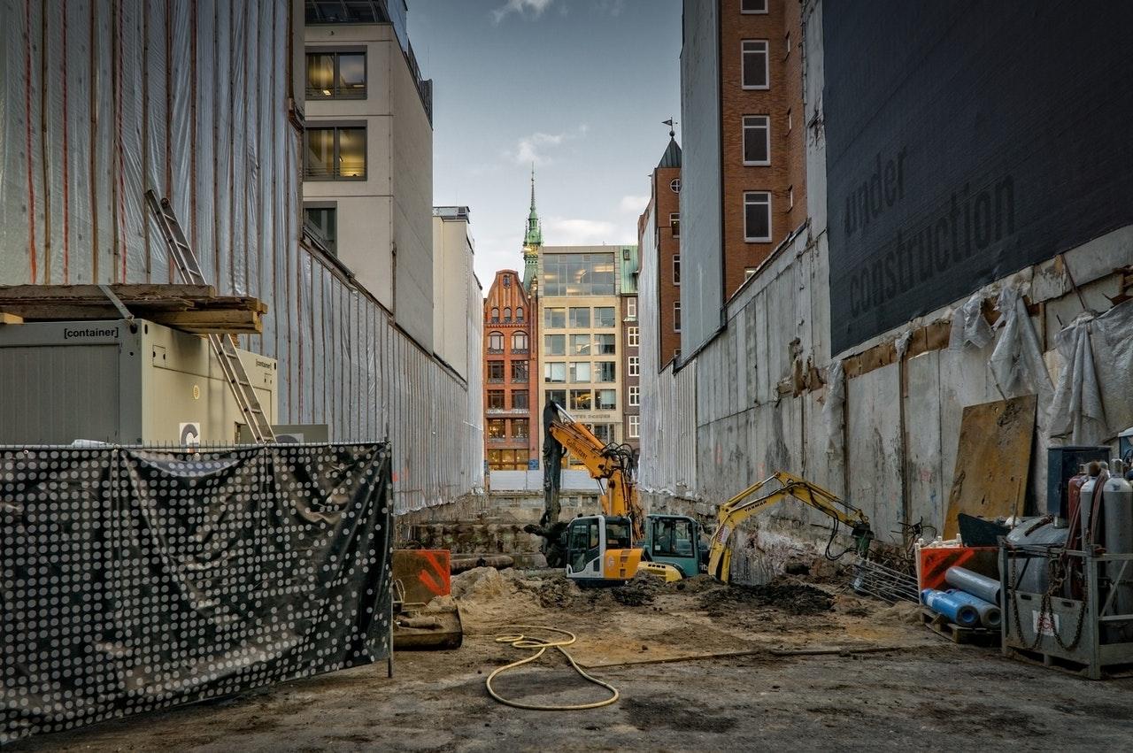 Rue en chantier, bâtiment en construction et peleteuse