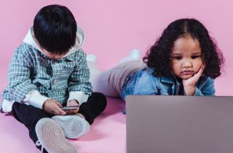 Enfant jouant sur ordinateur et téléphone