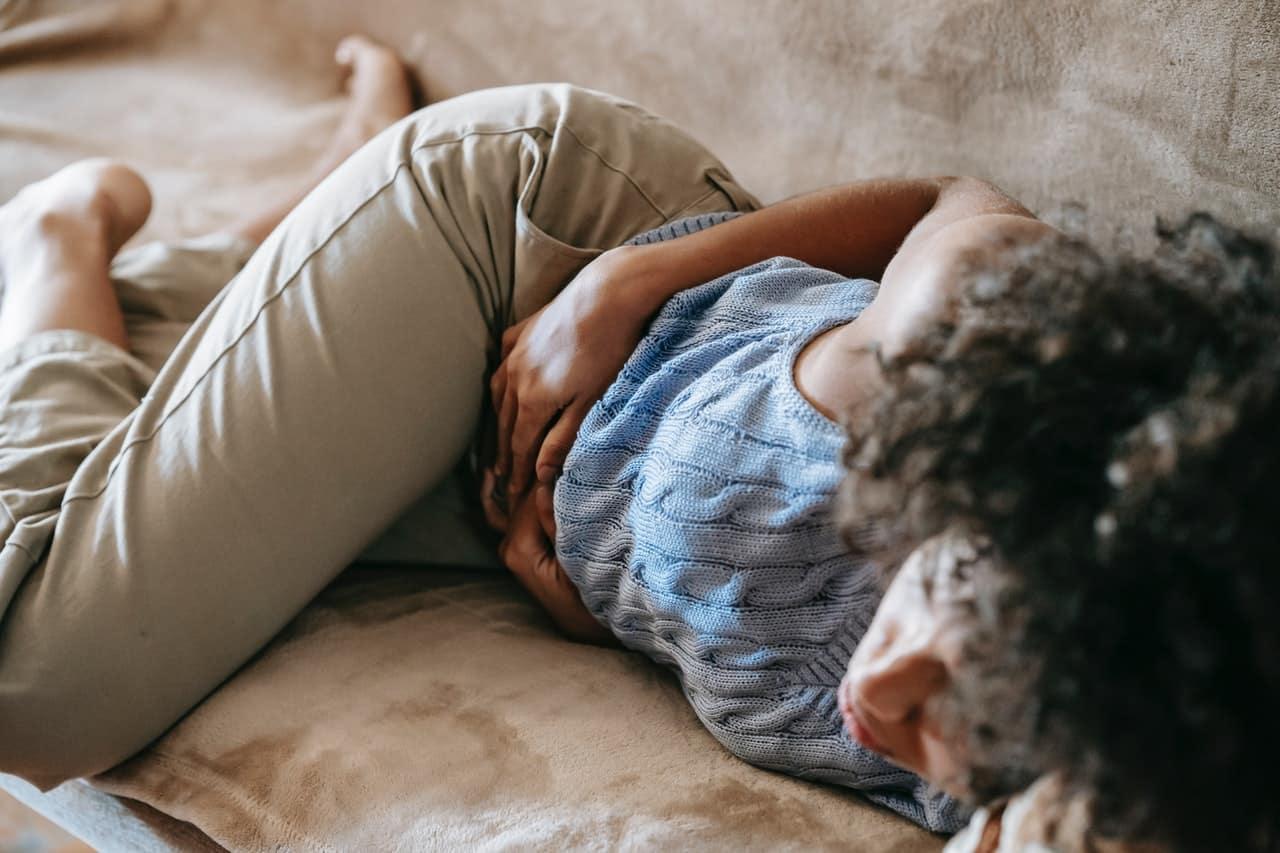 Femme allongée se tenant le ventre mal-être