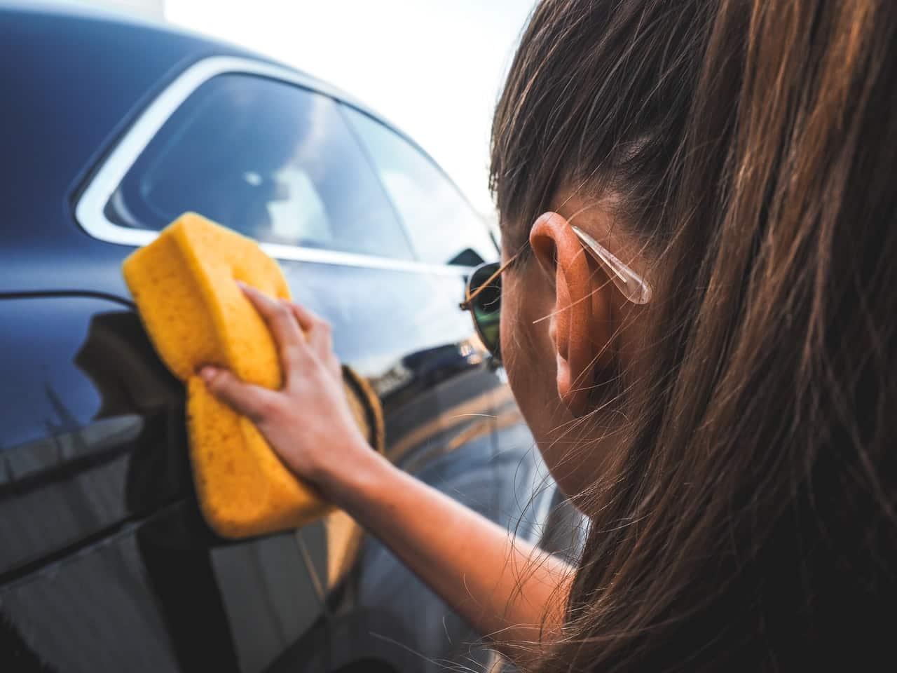 Femme lavant la carrosserie d'une voiture avec une grosse éponge jaune