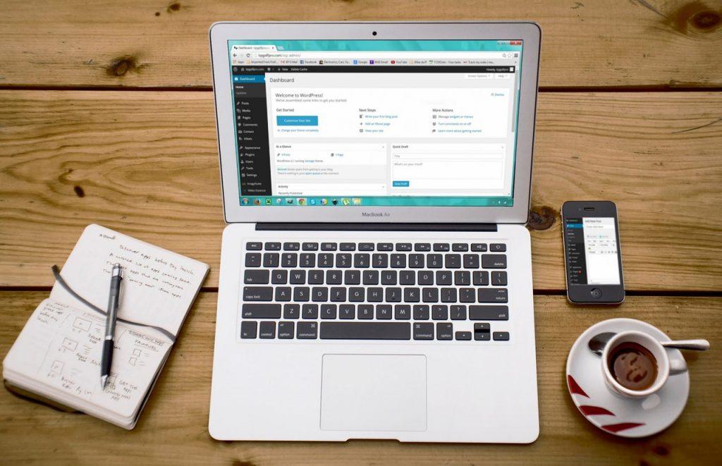 Ordinateur posé sur une table avec bloc note, tasse de café et iPhone