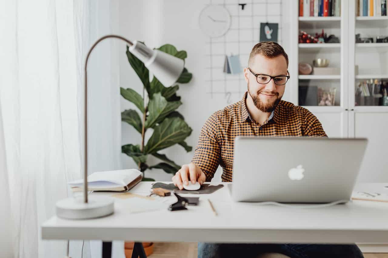 Homme heureux et souriant devant son ordinateur sur son bureau