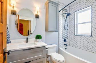 Salle de bain simple, avec sanitaire, toilette, baignoire, miroir rond