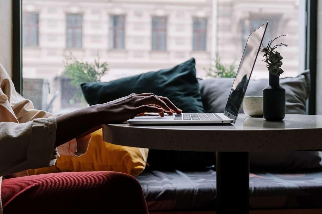 Personne sur une table basse devant un ordinateur