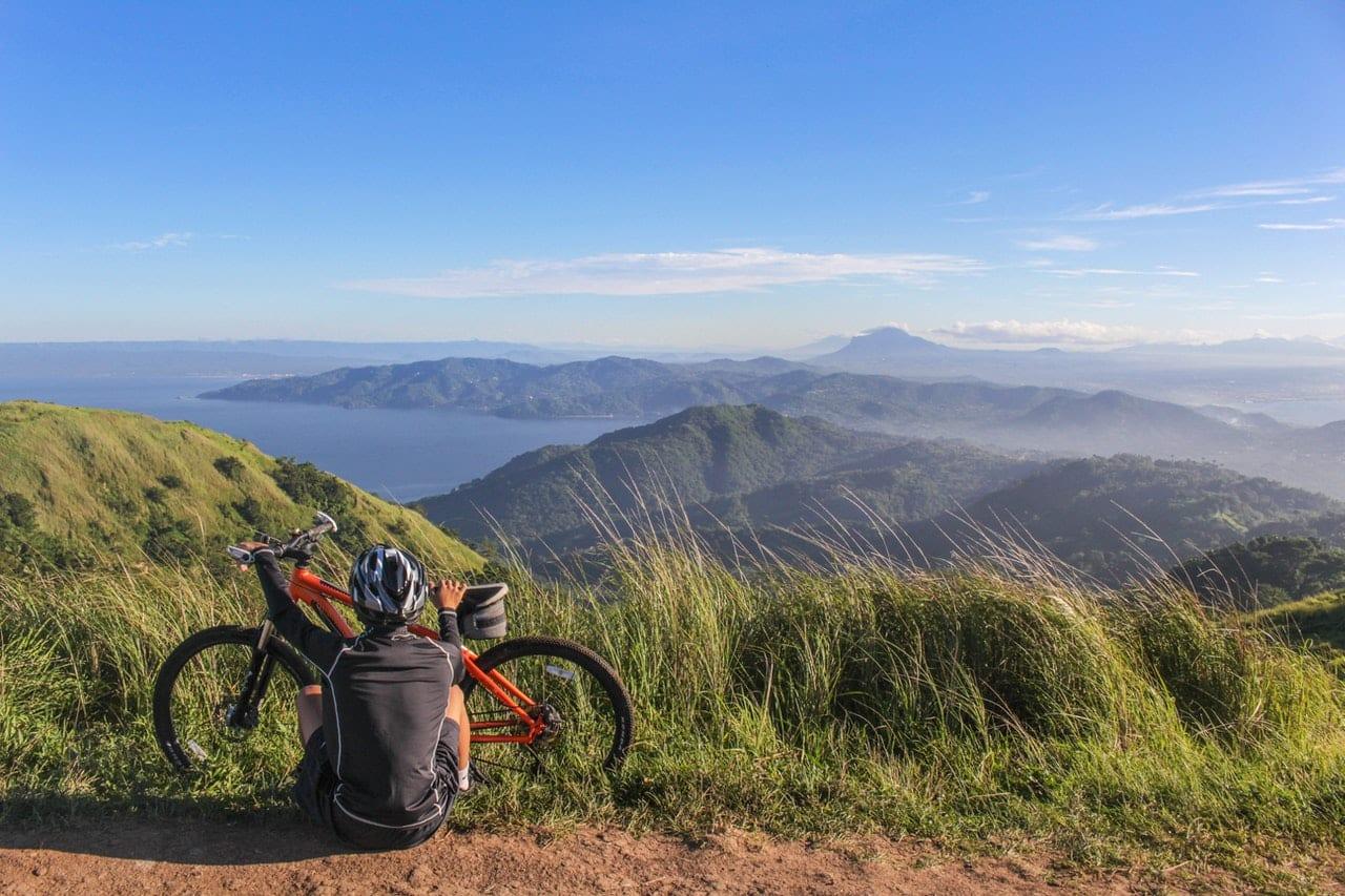 Homme assis avec son VTT regardant la vue panoramic des montagnes