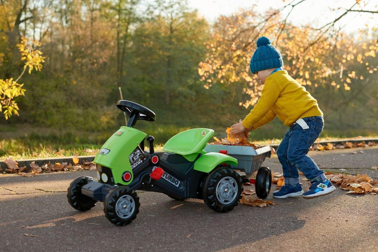 Petit garçon poussant un tracteur à pédales vert
