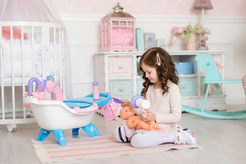 Petite fille jouant à la maman avec une poupée corole
