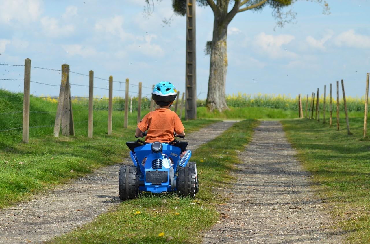 Enfant faisant du quad en promenade sur un chemin