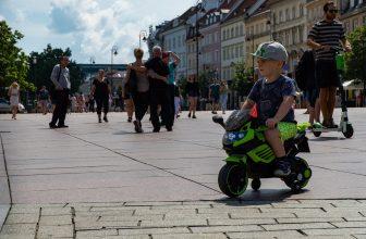 Petit garçon sur une moto 3 roues en ville